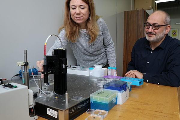 Los investigadores Elisabet Xifré y Lluís Marsal, ante el aparato de espectroscopia de reflectancia interferométrica que han utilizado para desarrollar el sensor, un método óptico que permite detectar niveles de señal ínfimos Fuente: URV