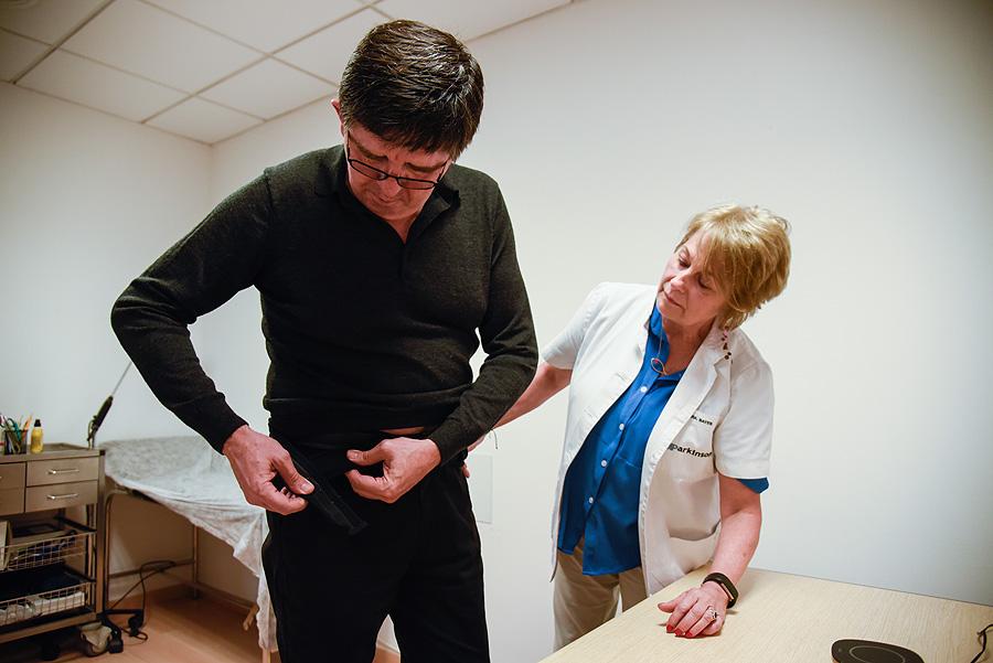 Jordi Homs se pone el cinturón equipado con el holter STAT-ON, con la ayuda de la Dra. Àngels Bayés Fuente: Centro Médico Teknon-Quirónsalud / Sense4Care / UPC