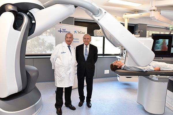 El Dr. Josep Ramon Armengol (a la izq. de la imagen) e Isidre Fainé, presidente de la Fundación Bancaria 'la Caixa', posando bajo el nuevo robot